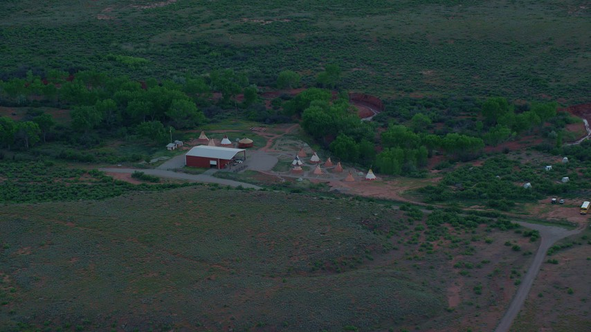 6K stock footage aerial video of approaching a small desert museum with teepees, Moab, Utah, twilight Aerial Stock Footage | AX138_453