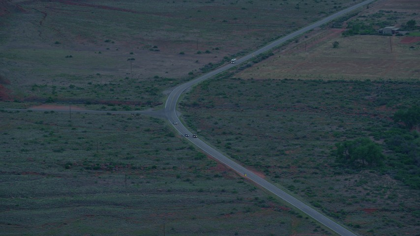 6K stock footage aerial video of tracking cars on State Route 128 through desert valley, Moab, Utah, twilight Aerial Stock Footage | AX138_457