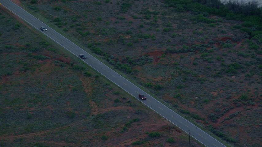 6K stock footage aerial video track SUV, two sedans on State Route 128, Moab, Utah, twilight Aerial Stock Footage | AX138_458