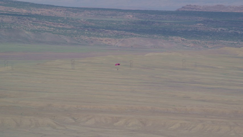 6K stock footage aerial video of tracking skydiver descending over desert valley, Canyonlands Field, Utah Aerial Stock Footage | AX139_014