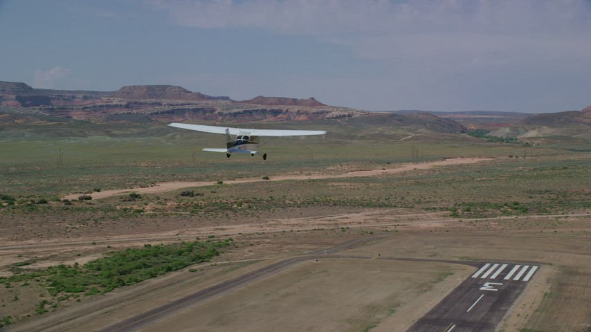 6K stock footage aerial video of tracking a Cessna ascending over the end of runway, Canyonlands Field, Utah Aerial Stock Footage | AX139_022