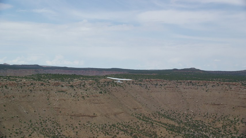 6K stock footage aerial video of a wide view of a Cessna flying by desert mesas, Emery County, Utah Aerial Stock Footage | AX139_106