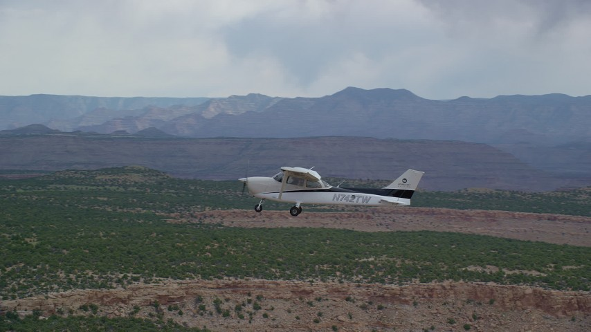 6K stock footage aerial video of a closer view of a Cessna flying by desert mesas, Emery County, Utah Aerial Stock Footage | AX139_109
