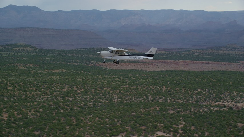 6K stock footage aerial video track a Cessna flying by desert mesas, Emery County, Utah Aerial Stock Footage | AX139_110
