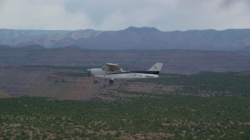 6K stock footage aerial video track a Cessna flying by desert mesas and distant mountains, Emery County, Utah Aerial Stock Footage | AX139_112