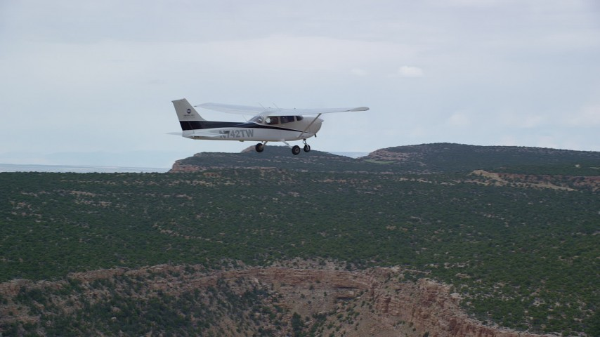 6K stock footage aerial video pan to reveal and track Cessna flying over desert mesas, Emery County, Utah Aerial Stock Footage | AX139_114
