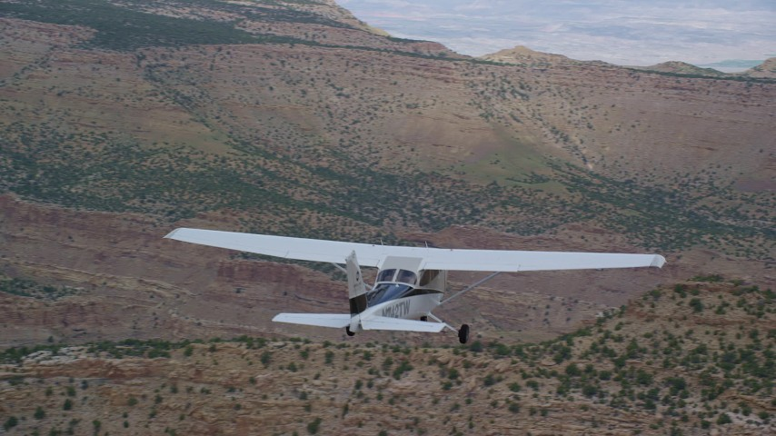 6K stock footage aerial video of tracking a Cessna flying over desert near wide canyon, Emery County, Utah Aerial Stock Footage | AX139_118