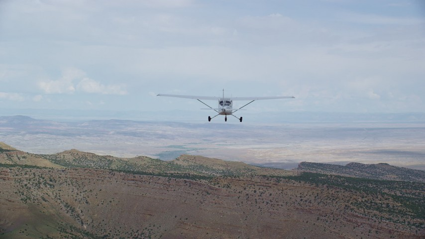 6K stock footage aerial video of tracking Cessna over desert near ridge, ascend out of frame, Emery County, Utah Aerial Stock Footage AX139_120 | Axiom Images