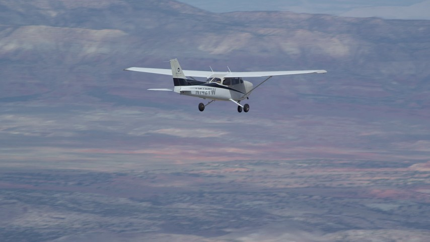 6K stock footage aerial video of Cessna airplane flying high above desert, partly cloudy, Emery County, Utah Aerial Stock Footage | AX139_126