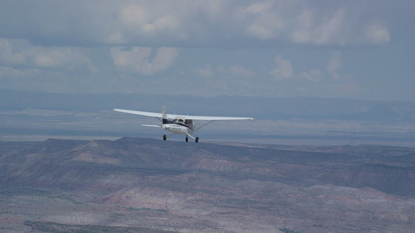 6K stock footage aerial video of focusing on a Cessna airplane flying high above desert, partly cloudy, Emery County, Utah Aerial Stock Footage | AX139_129