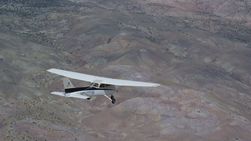 6K stock footage aerial video focus on a Cessna in flight high above desert vegetation, Emery County, Utah Aerial Stock Footage AX139_132 | Axiom Images