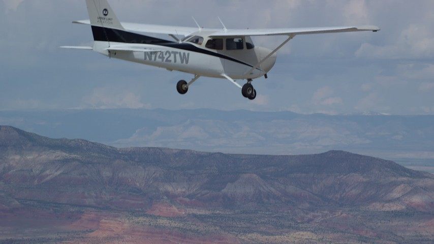 6K stock footage aerial video reveal and track Cessna flying high above desert mountains, Emery County, Utah Aerial Stock Footage | AX139_134
