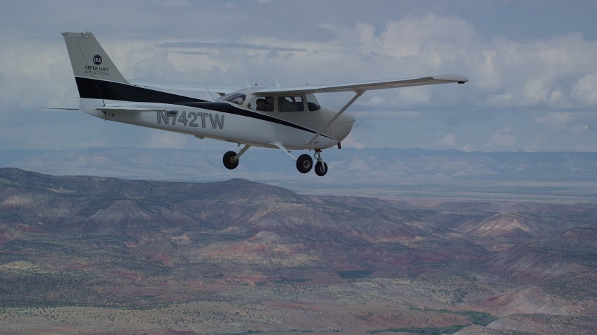 6K stock footage aerial video of flying beside a Cessna high above desert, partly cloudy skies, Emery County, Utah Aerial Stock Footage | AX139_138