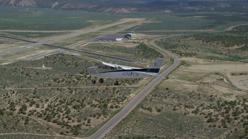 6K stock footage aerial video of a Cessna airplane flying over desert near airport, Buck Davis Field, Utah Aerial Stock Footage | AX139_160