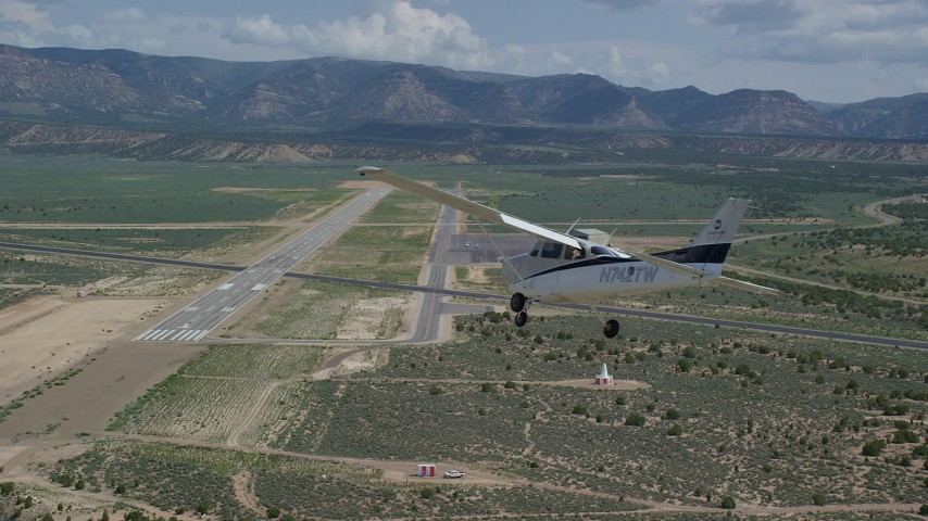 6K stock footage aerial video of a Cessna aircraft flying over desert near airport, Buck Davis Field, Utah Aerial Stock Footage | AX139_161