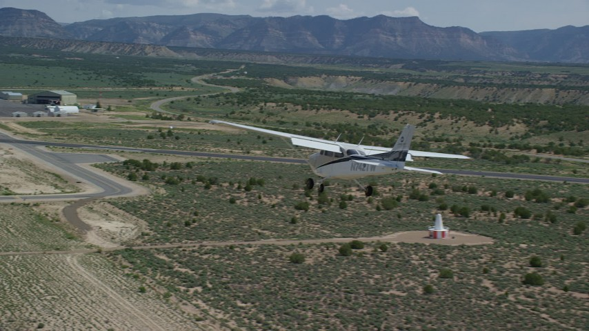 6K stock footage aerial video of tracking a Cessna flying over desert and approaching Buck Davis Field, Utah Aerial Stock Footage | AX139_162