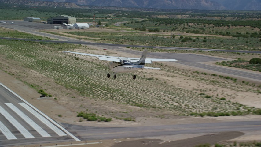6K stock footage aerial video of tracking a Cessna coming in for landing at Buck Davis Field, Utah Aerial Stock Footage | AX139_163