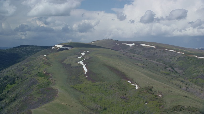 6K stock footage aerial video of flying by mountains with snow patches beneath partly cloudy skies, Utah County, Utah Aerial Stock Footage | AX140_036
