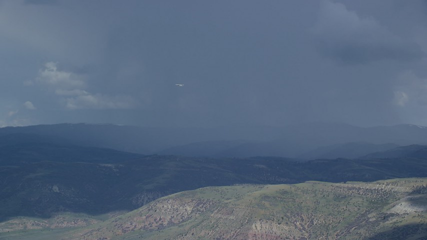 Tracking Tecnam P2006T flying by rainstorm, cloudy, Wasatch Range, Utah Aerial Stock Footage | AX140_039