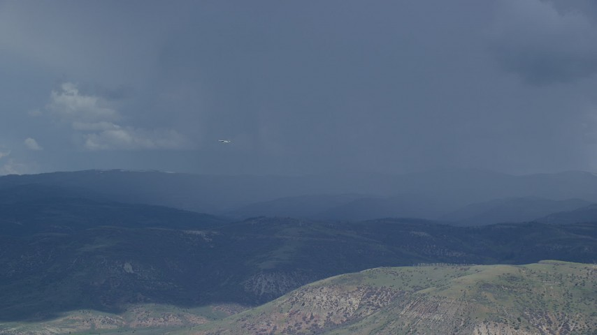 6K stock footage aerial video of a Tecnam P2006T airplane flying by rainstorm, Wasatch Range, Utah Aerial Stock Footage | AX140_040