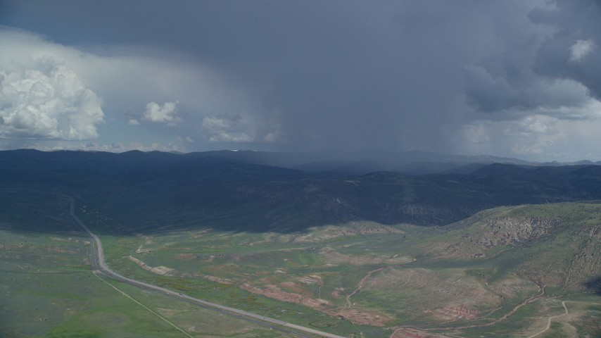 6K stock footage aerial video track a distant Tecnam P2006T by a rainstorm and Highway 6, Wasatch Range, Utah County, Utah Aerial Stock Footage | AX140_042