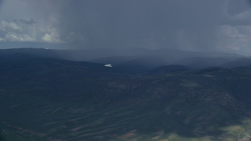 Tracking Tecnam P2006T flying by rainstorm, Wasatch Range, Utah Aerial Stock Footage | AX140_044