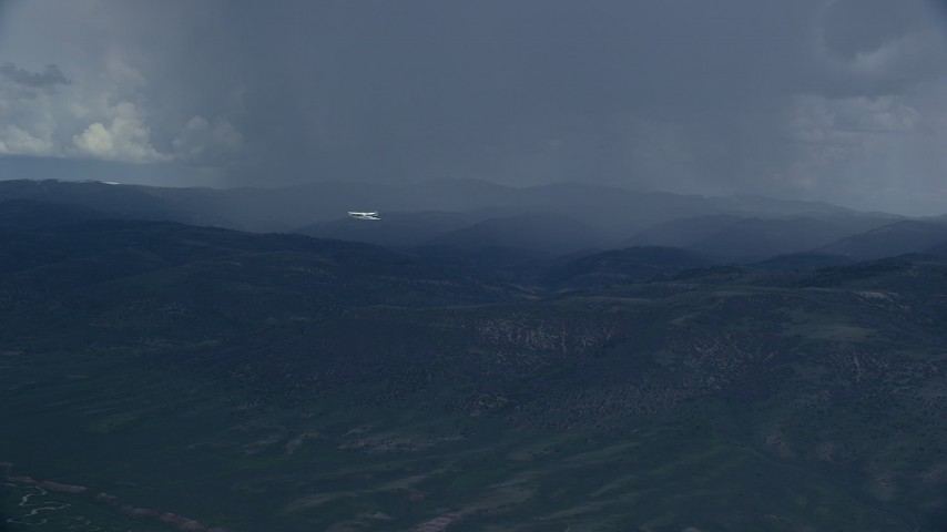 6K stock footage aerial video of a Tecnam P2006T aircraft flying by rainstorm in the Wasatch Range, Utah Aerial Stock Footage | AX140_045