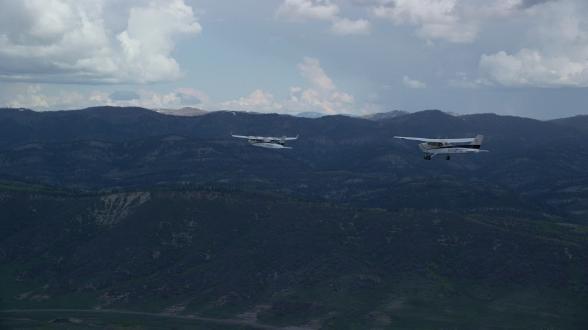 Tracking Tecnam P2006T, Cessna flying by mountains, cloudy, Wasatch Range, Utah Aerial Stock Footage | AX140_050