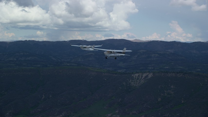 6K stock footage aerial video of focusing on Tecnam P2006T and Cessna passing mountains in the Wasatch Range, Utah Aerial Stock Footage | AX140_051