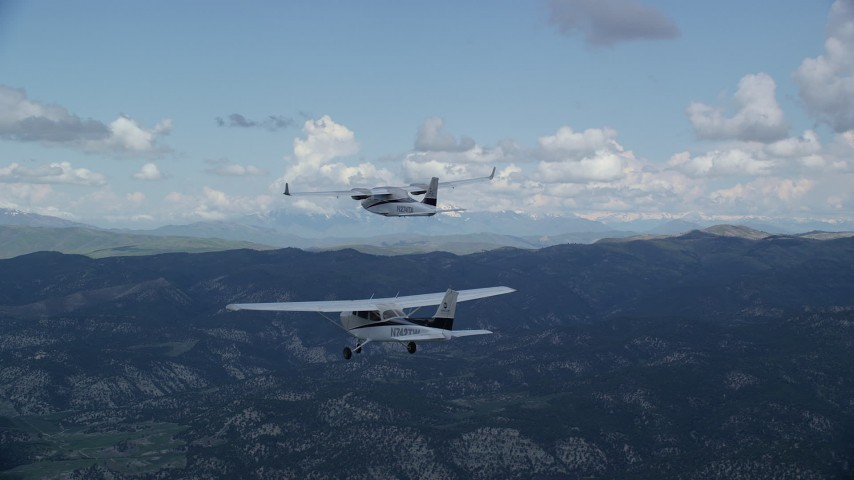 Tracking Tecnam P2006T, Cessna flying by mountains, cloudy, Wasatch Range, Utah Aerial Stock Footage | AX140_061
