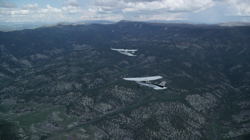 6K stock footage aerial video of a Tecnam P2006T in the lead with a Cessna over mountains, Wasatch Range, Utah Aerial Stock Footage | AX140_067