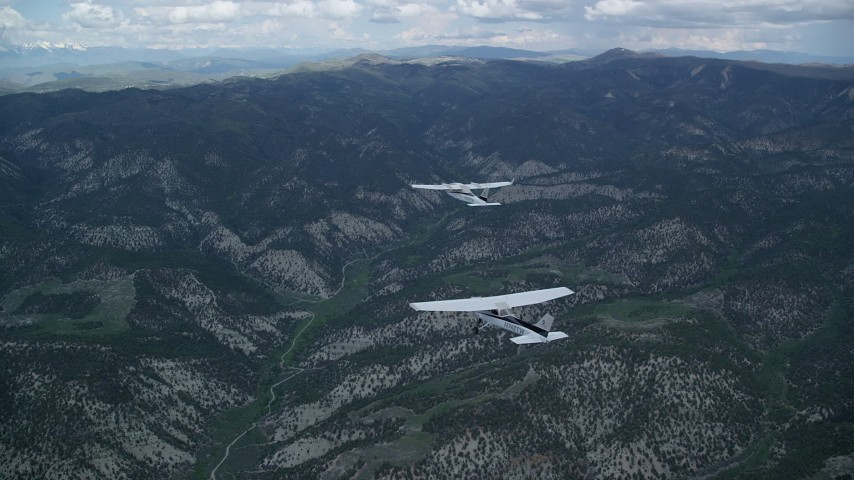 6K stock footage aerial video of a Tecnam P2006T airplane leading a Cessna over Wasatch Range, Utah Aerial Stock Footage | AX140_068