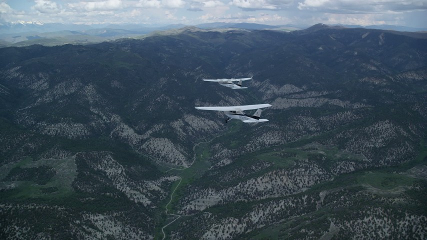 6K stock footage aerial video tracking Tecnam P2006T flying ahead of Cessna over mountains, Wasatch Range, Utah Aerial Stock Footage | AX140_069