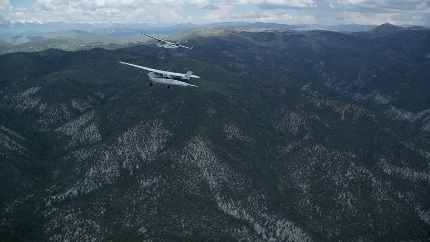 6K stock footage aerial video of following a Cessna tailing a Tecnam P2006T over the Wasatch Range, Utah Aerial Stock Footage | AX140_072