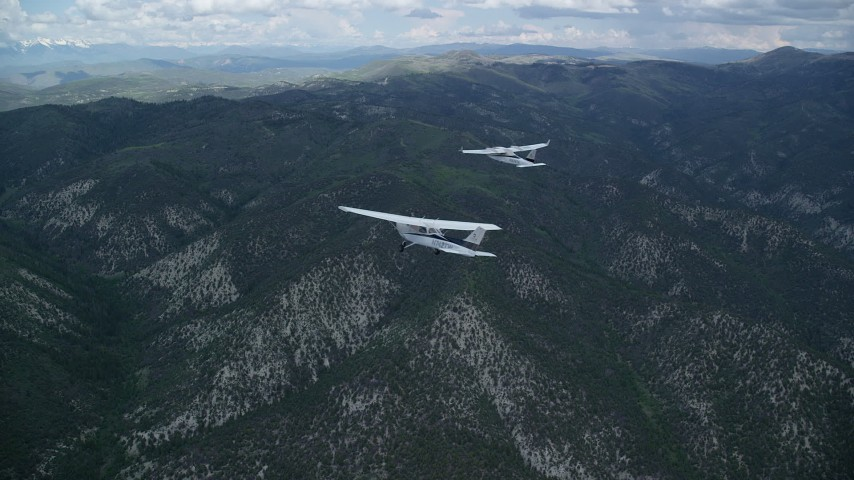 Tracking Tecnam P2006T, Cessna over mountains, cloudy, Wasatch Range, Utah Aerial Stock Footage   AX140_073