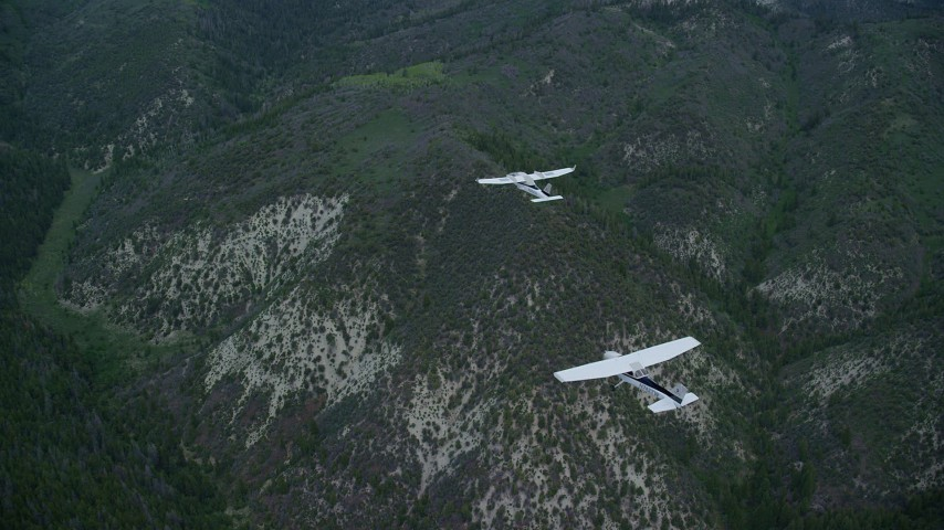 Tracking Tecnam P2006T, Cessna over mountains, cloudy, Wasatch Range, Utah Aerial Stock Footage | AX140_074