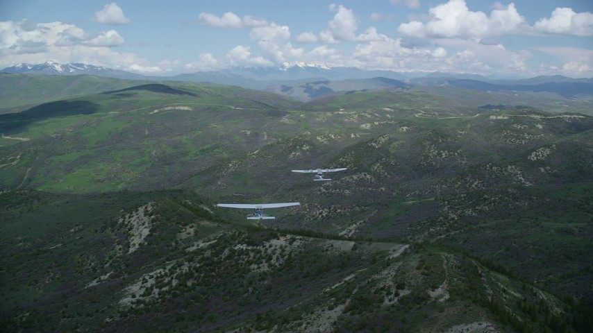 Tecnam P2006T, Cessna over mountains, pan right, clouds, Wasatch Range, Utah Aerial Stock Footage   AX140_078