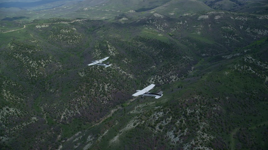Tecnam P2006T, Cessna over mountains, pan left, clouds, Wasatch Range, Utah Aerial Stock Footage   AX140_081
