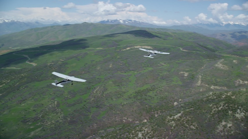 6K stock footage aerial video of flying around a Tecnam P2006T leading a Cessna over mountains, Wasatch Range, Utah Aerial Stock Footage | AX140_081