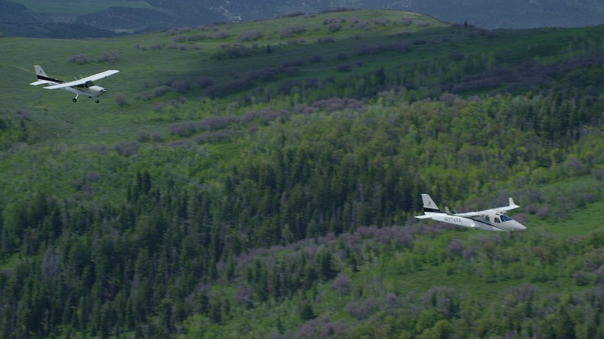 Tracking Tecnam P2006T, Cessna over mountains, zoom out, Wasatch Range, Utah Aerial Stock Footage   AX140_087