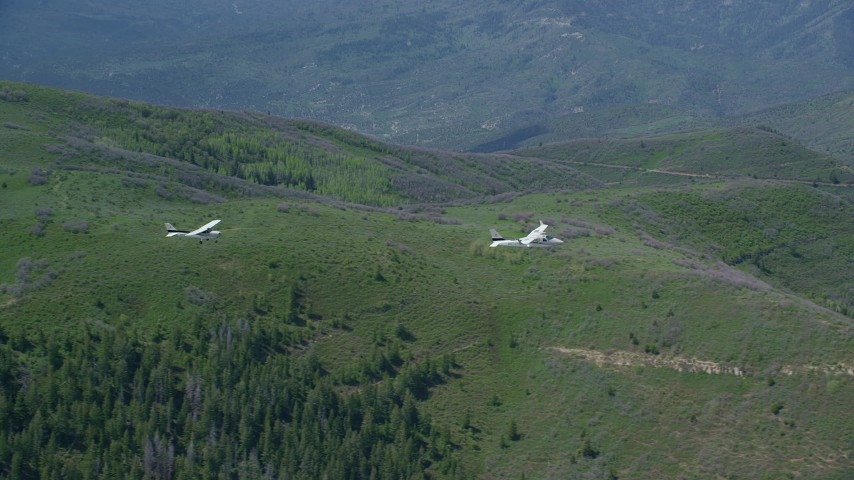 6K stock footage aerial video of tracking Tecnam P2006T and Cessna aircraft over mountains and trees, Wasatch Range, Utah Aerial Stock Footage | AX140_089
