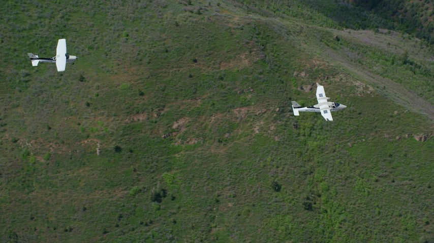 6K stock footage aerial video of tracking a Tecnam P2006T leading a Cessna over mountains, trees, Wasatch Range, Utah Aerial Stock Footage | AX140_091