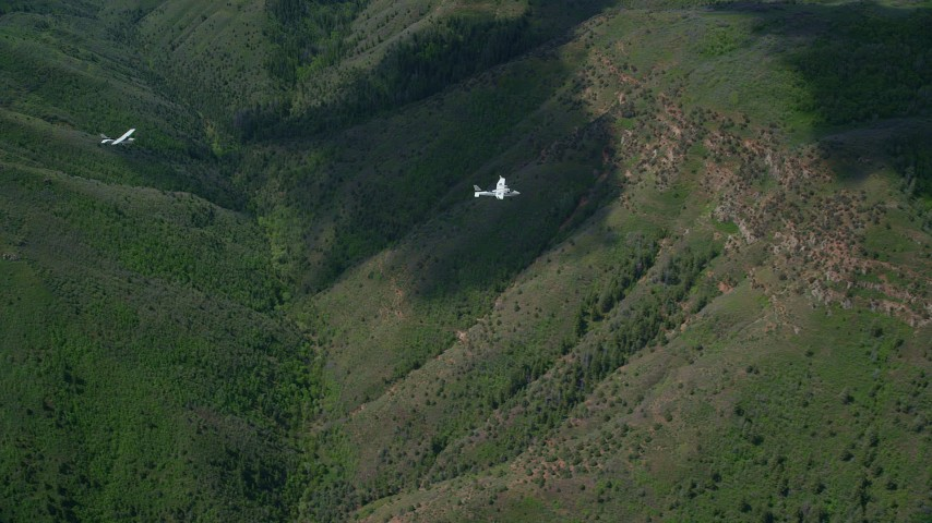 Tracking Tecnam P2006T, Cessna over mountains, trees, Wasatch Range, Utah Aerial Stock Footage | AX140_092