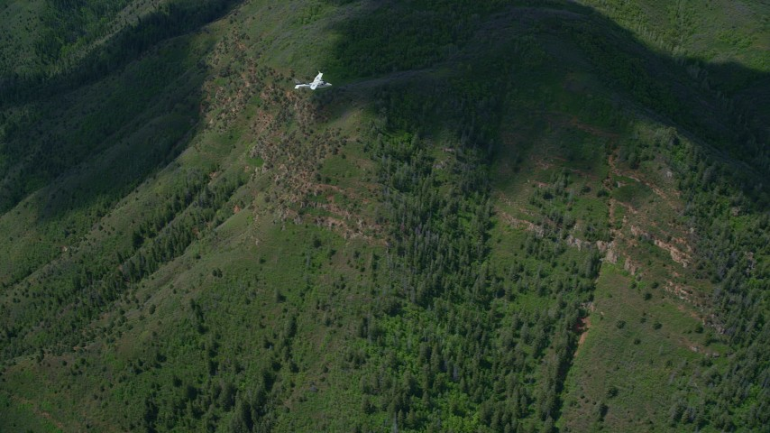 6K stock footage aerial video of a Tecnam P2006T and Cessna in flight over mountains, trees, Wasatch Range, Utah Aerial Stock Footage | AX140_093