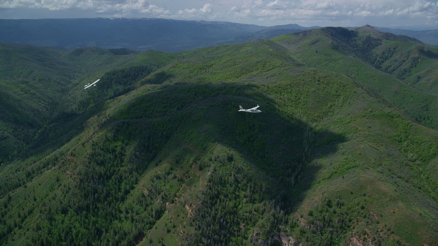Tracking Tecnam P2006T, Cessna over mountains, trees, Wasatch Range, Utah Aerial Stock Footage | AX140_094