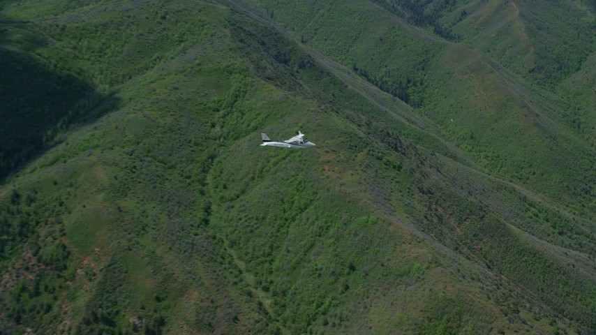 Tracking Tecnam P2006T over mountains, zoom in, Wasatch Range, Utah Aerial Stock Footage | AX140_095