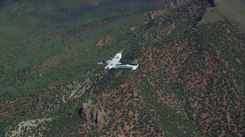 Tracking Tecnam P2006T over green mountains, Wasatch Range, Utah Aerial Stock Footage   AX140_100