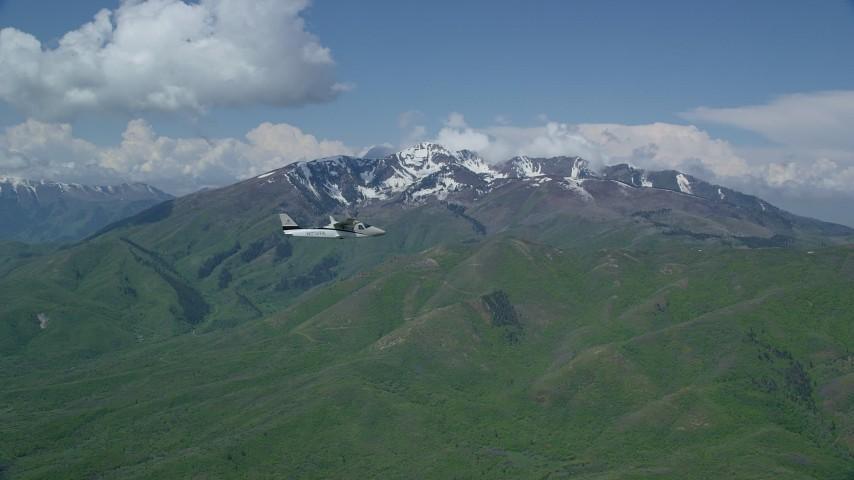 6K stock footage aerial video of a Tecnam P2006T in flight near near snowy Wasatch Range peak, Utah Aerial Stock Footage | AX140_108