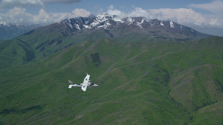 Tracking Tecnam P2006T flying near snowy peak, Wasatch Range, Utah Aerial Stock Footage | AX140_109