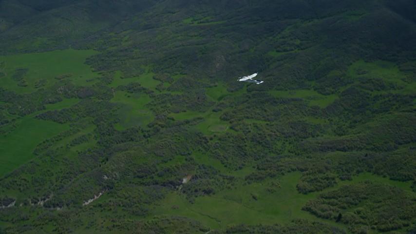 Tracking Tecnam P2006T near green mountain ridge, Wasatch Range, Utah Aerial Stock Footage   AX140_110